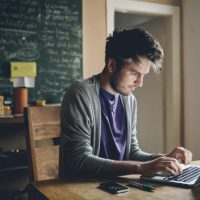 Vintage toned image of a young man working at home, freelancer, designer or writer, checking e-mails or typing on the laptop. Only natural light used, higher iso settings. Interior looks like a modern office, home or a co-working space.