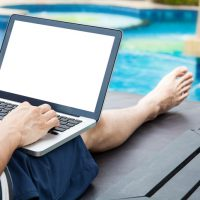 Screen mockup of laptop that a man is using in the pool on vacation - work anywhere and internet work concept
