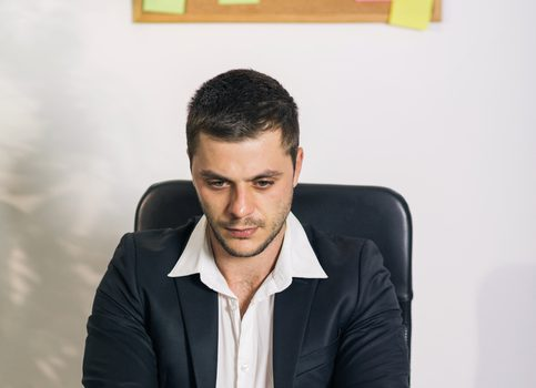 Young man, looking preoccupied and worried, sitting behind a desk in business office and working on a laptop